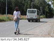 Купить «Балашиха, девушка на электрическом самокате движется по обочине дороги», эксклюзивное фото № 34345827, снято 3 августа 2020 г. (c) Дмитрий Неумоин / Фотобанк Лори