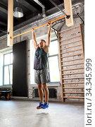 Купить «man exercising on bar and doing pull-ups in gym», фото № 34345999, снято 3 июля 2020 г. (c) Syda Productions / Фотобанк Лори