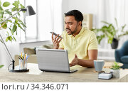 man recording voice on smartphone at home office. Стоковое фото, фотограф Syda Productions / Фотобанк Лори