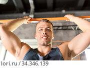 Купить «man exercising on bar and doing pull-ups in gym», фото № 34346139, снято 3 июля 2020 г. (c) Syda Productions / Фотобанк Лори
