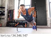man doing push-ups on gymnastic rings in gym. Стоковое фото, фотограф Syda Productions / Фотобанк Лори