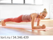 woman doing yoga in forearm plank pose at home. Стоковое фото, фотограф Syda Productions / Фотобанк Лори