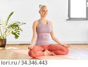 woman meditating in lotus yoga pose at home. Стоковое фото, фотограф Syda Productions / Фотобанк Лори