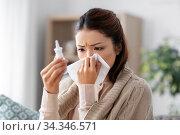 sick asian woman with nasal spray medicine at home. Стоковое фото, фотограф Syda Productions / Фотобанк Лори