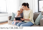 mother, daughter and grandma with tablet pc. Стоковое фото, фотограф Syda Productions / Фотобанк Лори