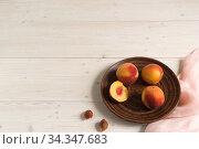 Персики в темной глиняной тарелке на белом деревянном столе. Стоковое фото, фотограф Наталья Гармашева / Фотобанк Лори