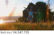 Woman with long braids slowly dancing on sunset meadow. Стоковое видео, видеограф Константин Шишкин / Фотобанк Лори