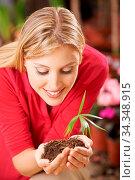 Frau hält kleine Pflanze mit Wurzel und Erde in den Händen als Symbol... Стоковое фото, фотограф Zoonar.com/Robert Kneschke / age Fotostock / Фотобанк Лори