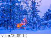 Winter in Finnish Lapland. The light of a lonely cottage in the dense... Стоковое фото, фотограф Mykhailo V. Pavlov / easy Fotostock / Фотобанк Лори