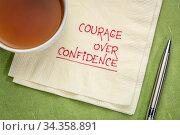 Courage over confidence doodle - handwriting on a napkin with cup... Стоковое фото, фотограф Zoonar.com/Marek Uliasz / easy Fotostock / Фотобанк Лори