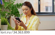 asian woman with smartphone and flowers at home. Стоковое видео, видеограф Syda Productions / Фотобанк Лори