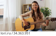 young woman with guitar videoblogging at home. Стоковое видео, видеограф Syda Productions / Фотобанк Лори