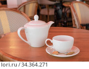 White porcelain teapot and tea cup stand on a table in a cafe. Стоковое фото, фотограф Ольга Губская / Фотобанк Лори