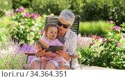 Купить «grandmother and baby granddaughter reading book», видеоролик № 34364351, снято 28 июля 2020 г. (c) Syda Productions / Фотобанк Лори