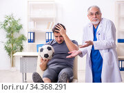 Young injured soccer player visiting old doctor traumatologist. Стоковое фото, фотограф Elnur / Фотобанк Лори