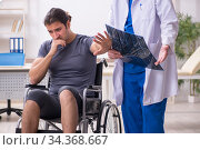 Young male patient in wheel-chair visiting old doctor radiologis. Стоковое фото, фотограф Elnur / Фотобанк Лори