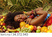 African American Black woman smiling with closed eyes while lying among fruits. Стоковое фото, фотограф Алексей Кузнецов / Фотобанк Лори