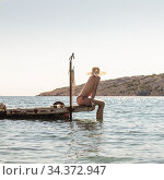 View of unrecognizable woman wearing big summer sun hat tanning topless and relaxing on old wooden pier in remote calm cove of Adriatic sea, Croatia. Стоковое фото, фотограф Matej Kastelic / Фотобанк Лори