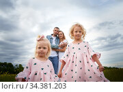 A family including two young parents and daughters on a walk in a meadow with grass and flowers. Dad, mom, girls relaxing and having fun in nature on a summer day with clouds. Стоковое фото, фотограф Кривошеина Елена Леонидовна / Фотобанк Лори