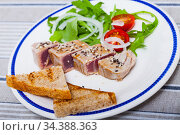 Tasty lightly fried tuna, served at plate with bread and greens. Стоковое фото, фотограф Яков Филимонов / Фотобанк Лори