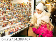 Female customers staring at counter of kiosk with figures for creating miniature Christmas scenes. Стоковое фото, фотограф Яков Филимонов / Фотобанк Лори