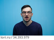 Portrait of an emotional young man in glasses shocked by low prices and discounts on a blue background. Стоковое фото, фотограф Pavel Biryukov / Фотобанк Лори