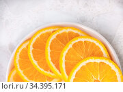 Half a plate with round slices of juicy orange on the table close up. Стоковое фото, фотограф Катерина Белякина / Фотобанк Лори
