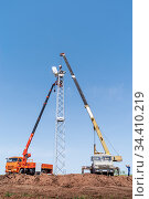 Orenburg, Russia - May, 26, 2020: Construction site, workers using construction equipment install a wind turbine tower. Редакционное фото, фотограф Вадим Орлов / Фотобанк Лори