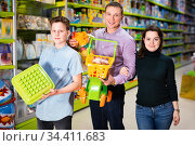 Portrait of friendly family with teenage son holding new toys purchased in kids mall. Стоковое фото, фотограф Яков Филимонов / Фотобанк Лори