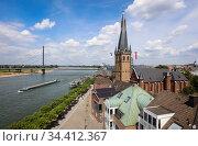 Rhine promenade with Lambertus church, in the back a cargo ship on the Rhine and the Oberkasseler bridge, Duesseldorf, North Rhine-Westphalia, Germany. Редакционное фото, агентство Caro Photoagency / Фотобанк Лори