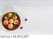 Несколько персиков в тарелке на белом деревянном столе. Свободное место для текста. Стоковое фото, фотограф Наталья Гармашева / Фотобанк Лори