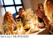 happy friends with red wine at christmas party. Стоковое фото, фотограф Syda Productions / Фотобанк Лори