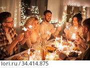 happy friends having christmas dinner at home. Стоковое фото, фотограф Syda Productions / Фотобанк Лори