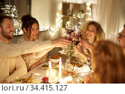 happy friends drinking red wine at christmas party. Стоковое фото, фотограф Syda Productions / Фотобанк Лори