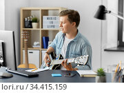 young man with computer playing guitar at home. Стоковое фото, фотограф Syda Productions / Фотобанк Лори