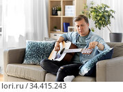young man playing guitar sitting on sofa at home. Стоковое фото, фотограф Syda Productions / Фотобанк Лори