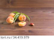 Несколько спелых персиков на коричневом деревянном столе. Свободное место для текста. Стоковое фото, фотограф Наталья Гармашева / Фотобанк Лори