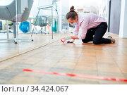 Geschäftsfrau mit Klebeband auf Büro Fußboden als Hinweis zum Abstand... Стоковое фото, фотограф Zoonar.com/Robert Kneschke / age Fotostock / Фотобанк Лори
