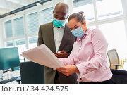 Zwei Business Leute im Büro mit Mund-Nasen-Schutz wegen Covid-19 ... Стоковое фото, фотограф Zoonar.com/Robert Kneschke / age Fotostock / Фотобанк Лори