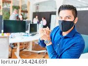 Junger Business Mann im Büro mit Mund-Nasen-Schutz wegen Covid-19... Стоковое фото, фотограф Zoonar.com/Robert Kneschke / age Fotostock / Фотобанк Лори