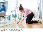 Geschäftsfrau markiert Boden im Büro mit Klebeband als Prävention... Стоковое фото, фотограф Zoonar.com/Robert Kneschke / age Fotostock / Фотобанк Лори