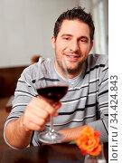 Mann prostet mit Glas Rotwein im Restaurant. Стоковое фото, фотограф Zoonar.com/Robert Kneschke / age Fotostock / Фотобанк Лори