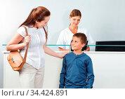 Mutter mit Sohn an der Theke beim Kinderarzt. Стоковое фото, фотограф Zoonar.com/Robert Kneschke / age Fotostock / Фотобанк Лори