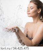 Young woman catching water splashes in her hands. Стоковое фото, фотограф Гурьянов Андрей / Фотобанк Лори