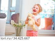 Lachendes Kind mit Kuscheltier in den Händen zu Hause. Стоковое фото, фотограф Zoonar.com/Robert Kneschke / age Fotostock / Фотобанк Лори