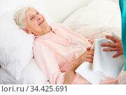 Seniorin im Bett wird von einem Altenpflegehelfer gewaschen. Стоковое фото, фотограф Zoonar.com/Robert Kneschke / age Fotostock / Фотобанк Лори