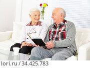 Senior liest seiner glücklichen Frau Geschichten aus einem Buch vor. Стоковое фото, фотограф Zoonar.com/Robert Kneschke / age Fotostock / Фотобанк Лори