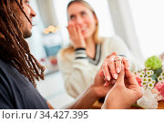 Mann macht einer glücklichen Frau Heiratsantrag mit Schenken vom ... Стоковое фото, фотограф Zoonar.com/Robert Kneschke / age Fotostock / Фотобанк Лори