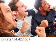 Jubelnde Sport Zuschauer jubeln zusammen in Bar oder Kneipe bei Fußballspiel. Стоковое фото, фотограф Zoonar.com/Robert Kneschke / age Fotostock / Фотобанк Лори