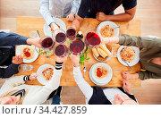 Gruppe Freunde beim Zuprosten mit Glas Wein beim Abendessen mit Spaghetti... Стоковое фото, фотограф Zoonar.com/Robert Kneschke / age Fotostock / Фотобанк Лори